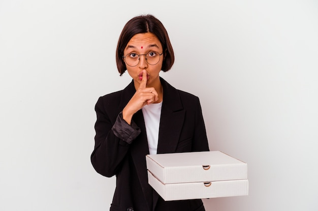 Młoda biznesowa indyjska kobieta trzyma pizze na białym tle, zachowując tajemnicę lub prosząc o ciszę.