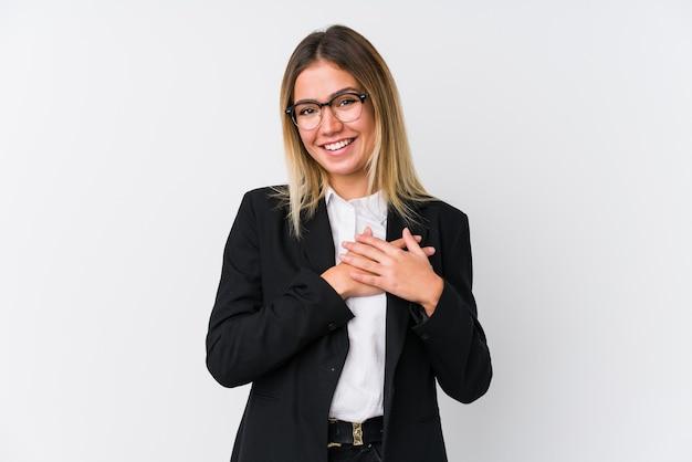 Młoda biznesowa kaukaska kobieta ma przyjazny wyraz twarzy, przyciskając dłoń do piersi. koncepcja miłości.