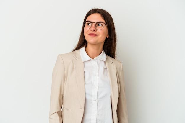Młoda biznesowa kaukaska kobieta na białym tle marzy o osiąganiu celów i celów
