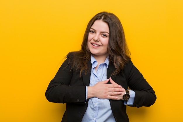 Młoda biznesowa kaukaska kobieta o dużych rozmiarach ma przyjazny wyraz, przyciskając dłoń do piersi. miłość .