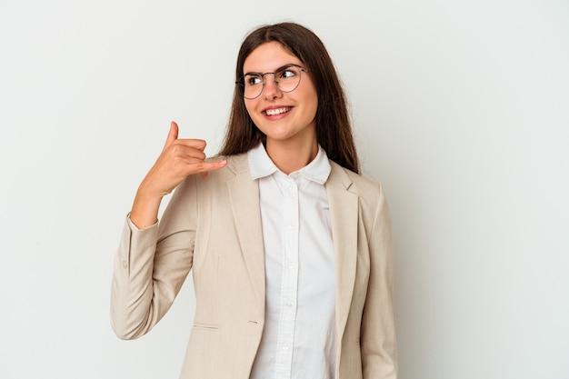 Młoda biznesowa kaukaska kobieta odizolowywająca na białym tle pokazuje gest rozmowy przez telefon komórkowy palcami.