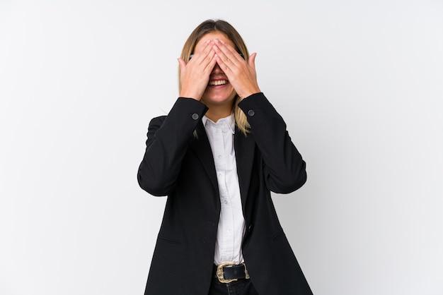 Młoda biznesowa kaukaska kobieta omija oczy rękami, uśmiecha się szeroko, czekając na niespodziankę.