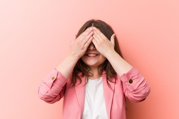 Młoda biznesowa kaukaska kobieta plus size zakrywa oczy dłońmi, uśmiecha się szeroko, czekając na niespodziankę.