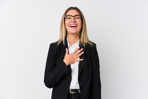 Młoda biznesowa kaukaska kobieta śmieje się głośno, trzymając rękę na piersi.