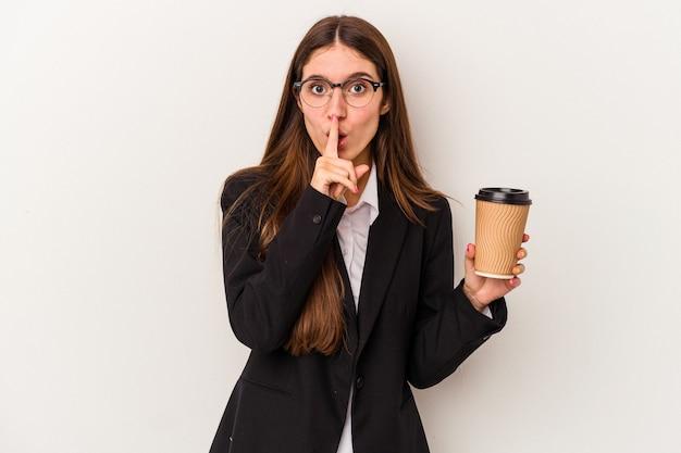 Młoda biznesowa kaukaska kobieta trzyma kawę na wynos na białym tle dochowując tajemnicy lub prosząc o ciszę.