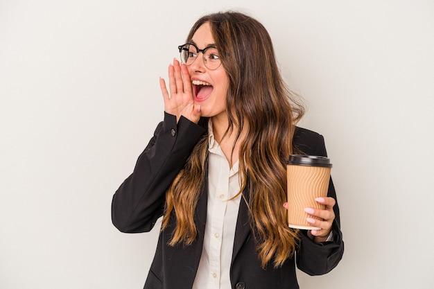 Młoda biznesowa kaukaska kobieta trzyma kawę na wynos na białym tle krzycząc i trzymając dłoń w pobliżu otwartych ust.