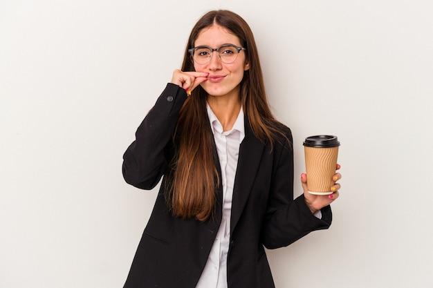 Młoda biznesowa kaukaski kobieta trzyma kawę na wynos na białym tle na białym tle z palcami na ustach zachowując tajemnicę.