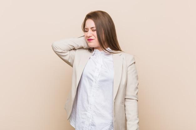 Młoda biznesowa kobieta cierpi ból szyi z powodu siedzącego trybu życia.