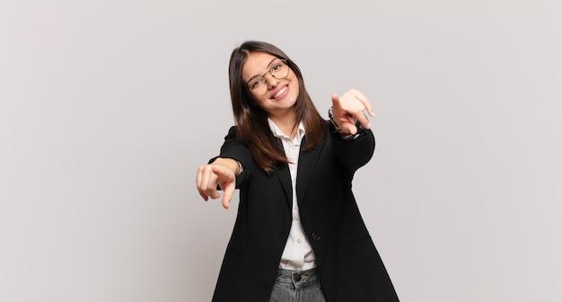 Młoda biznesowa kobieta czuje się szczęśliwa i pewna siebie, wskazując na aparat obiema rękami i śmiejąc się, wybierając ciebie