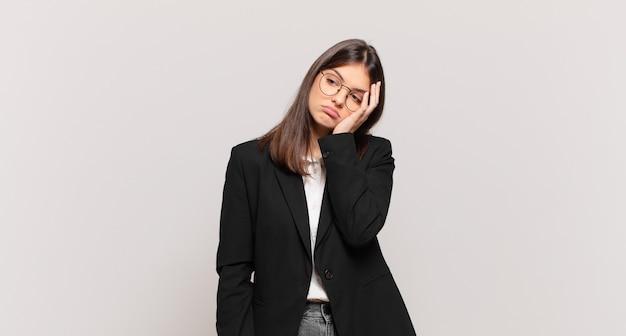 Młoda biznesowa kobieta czuje się znudzona, sfrustrowana i senna po męczącym, nudnym i żmudnym zadaniu, trzymając twarz ręką