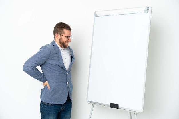 Młoda biznesowa kobieta daje prezentację na białej tablicy na białym tle