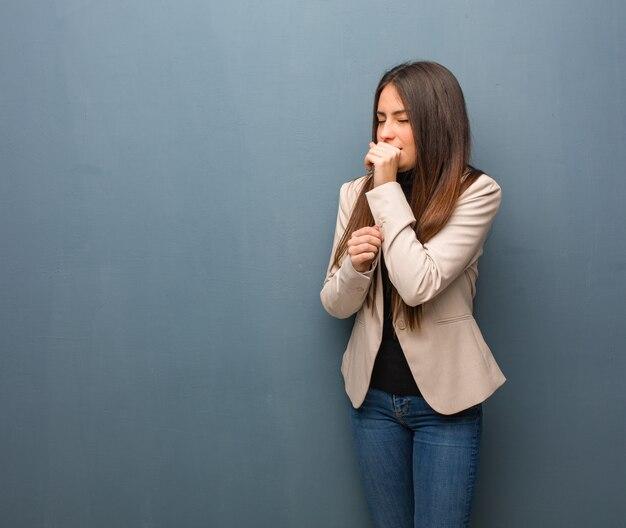 Młoda biznesowa kobieta kaszle, chora z powodu wirusa lub infekcji