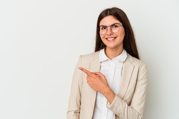 Młoda biznesowa kobieta kaukaska na białym tle uśmiecha się i wskazuje na bok, pokazując coś w pustej przestrzeni.