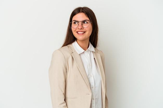 Młoda biznesowa kobieta kaukaska na białym tle wygląda na bok uśmiechniętą, wesołą i przyjemną.