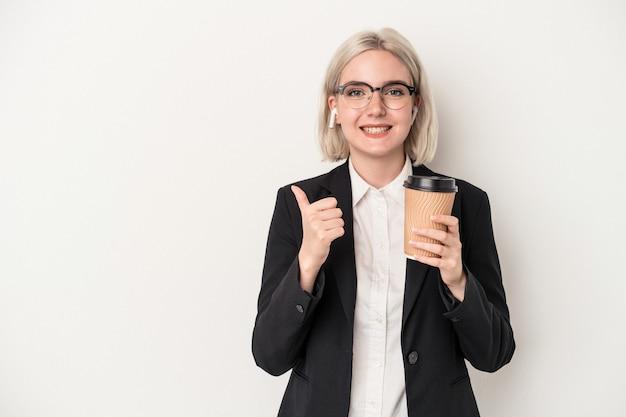 Młoda biznesowa kobieta kaukaska trzyma na wynos kawę na białym tle uśmiechając się i podnosząc kciuk w górę