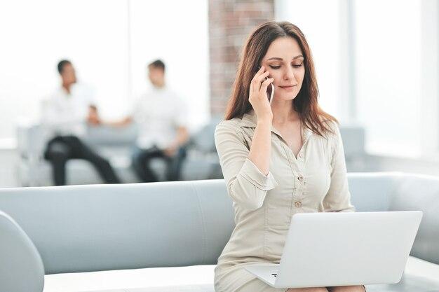 Młoda biznesowa kobieta komunikuje się ze swoimi partnerami za pomocą laptopa i smartfona. ludzie i technologia
