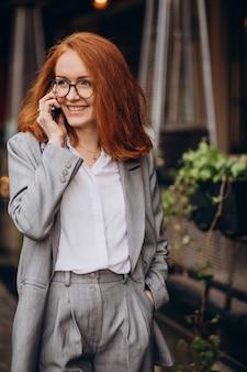 Młoda biznesowa kobieta korzysta z telefonu przy kawiarni