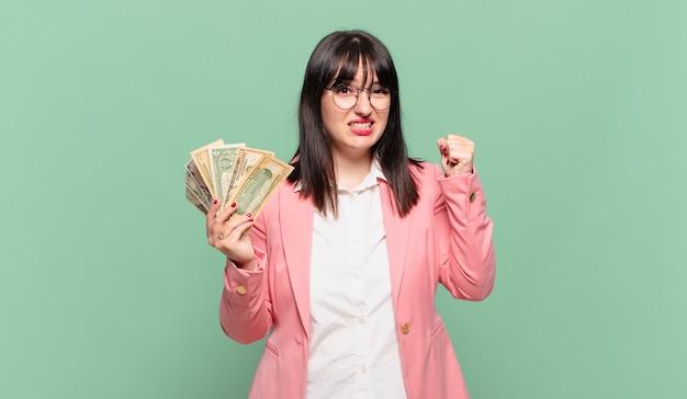 Młoda biznesowa kobieta krzyczy agresywnie z gniewnym wyrazem twarzy lub z zaciśniętymi pięściami świętuje sukces