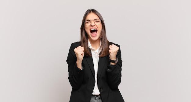 Młoda biznesowa kobieta krzyczy agresywnie ze zirytowanym, sfrustrowanym, gniewnym spojrzeniem i zaciśniętymi pięściami, czując się wściekły