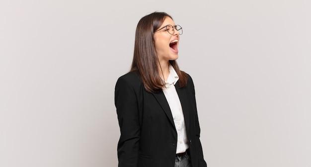 Młoda biznesowa kobieta krzyczy wściekle, krzyczy agresywnie, wygląda na zestresowaną i złą