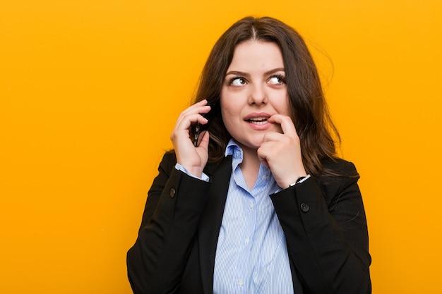 Młoda biznesowa kobieta krzywego plus rozmiar trzyma telefon zrelaksowany, myśląc o czymś patrząc na przestrzeń kopii.
