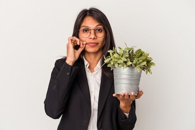 Młoda biznesowa kobieta łacińska gospodarstwa rośliny na białym tle z palcami na ustach zachowując tajemnicę.