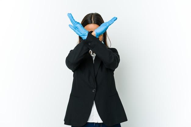 Młoda biznesowa kobieta łacińska ubrana w maskę, aby chronić przed covid na białej ścianie, trzymając skrzyżowane dwa ramiona, koncepcja odmowy.