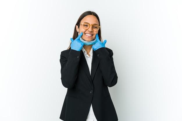Młoda biznesowa kobieta łacińska ubrana w maskę, aby chronić przed covid na białym tle wątpiąca między dwiema opcjami.