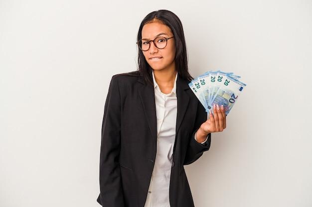 Młoda biznesowa kobieta latynoska trzymająca rachunki za kawę na białym tle zdezorientowana, czuje się wątpliwa i niepewna.