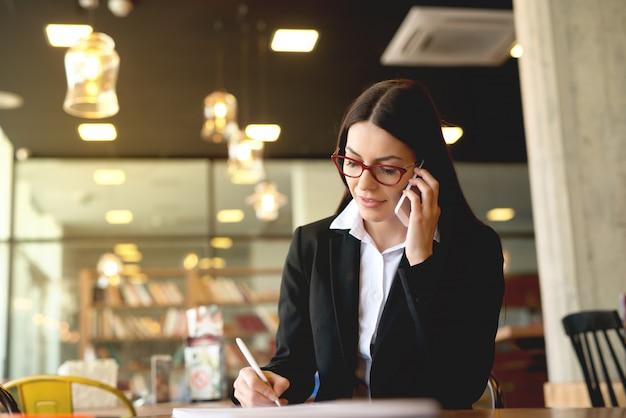 Młoda biznesowa kobieta ma rozmowę telefoniczną przy bufetem.