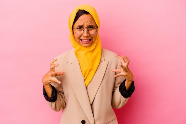 Młoda biznesowa kobieta muzułmańska na białym tle na różowym tle krzyczy z wściekłości.