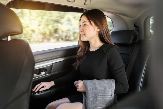 Młoda biznesowa kobieta myśli i wygląda na widok przez okno, siedząc na tylnym siedzeniu samochodu