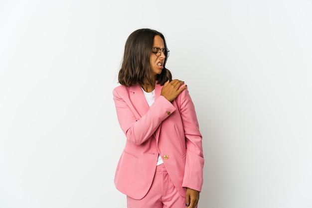 Młoda biznesowa kobieta na białym tle na białej ścianie masuje łokieć, cierpi po złym ruchu