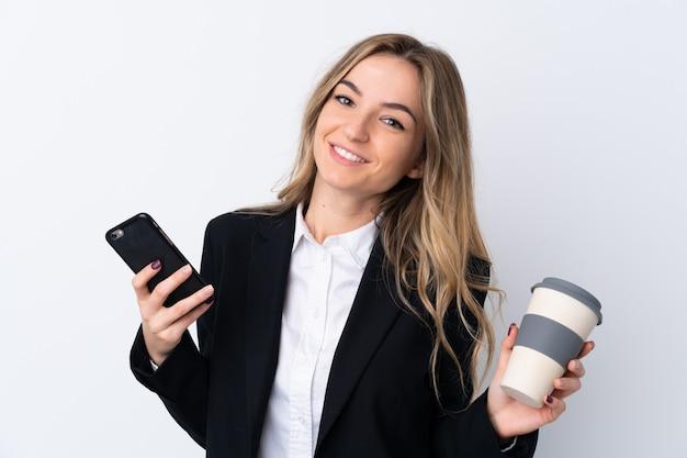 Młoda biznesowa kobieta nad odosobnioną biel ścianą trzyma filiżankę kawy i telefon