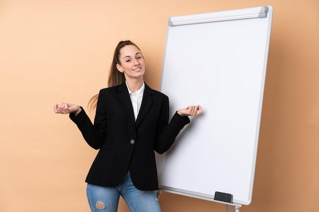 Młoda biznesowa kobieta nad odosobnioną ścianą daje prezentaci na białej desce