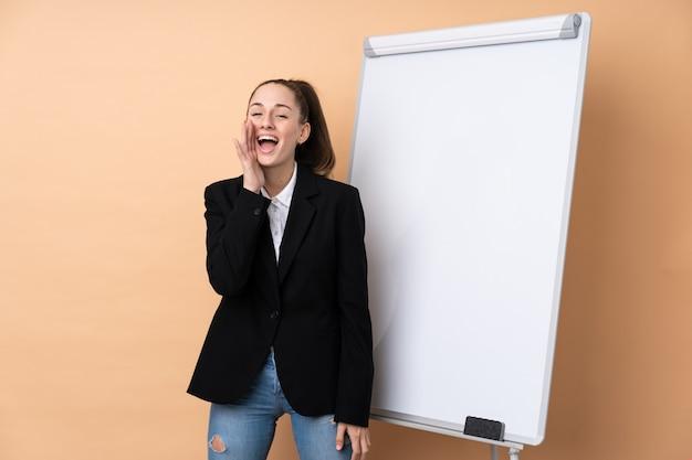 Młoda biznesowa kobieta nad odosobnionym wallgiving prezentacją na białej desce i krzyczeć z usta szeroko otwarty