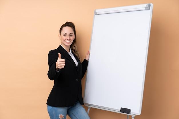 Młoda biznesowa kobieta nad odosobnionym wallgiving prezentacją na białej desce z kciukiem up