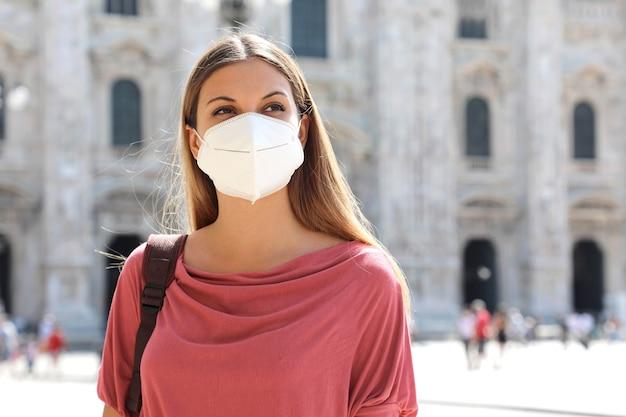 Młoda biznesowa kobieta nosząca maskę ochronną na wypadek rozprzestrzeniania się koronawirusa w mediolanie we włoszech