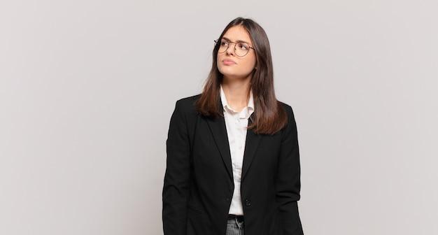 Młoda biznesowa kobieta o zmartwionej, zdezorientowanej, niezorientowanej twarzy, patrząca w górę, by skopiować przestrzeń, wątpiąca
