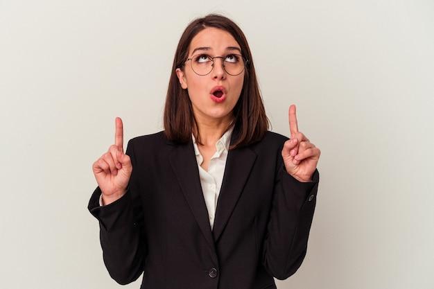 Młoda biznesowa kobieta odizolowywająca na białym tle wskazuje do góry z otwartymi ustami.