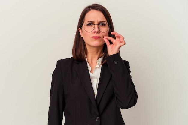 Młoda biznesowa kobieta odizolowywająca na białym tle z palcami na ustach zachowując sekret.