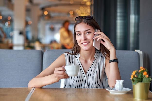 Młoda biznesowa kobieta opowiada na telefonie w sklep z kawą