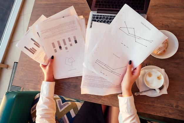 Młoda biznesowa kobieta pije kawę i pracuje na laptopie z papierami. pojęcie terminu