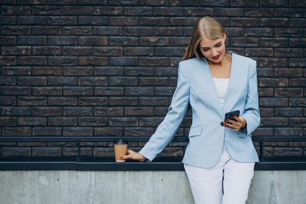 Młoda biznesowa kobieta pije kawę i rozmawia przez telefon