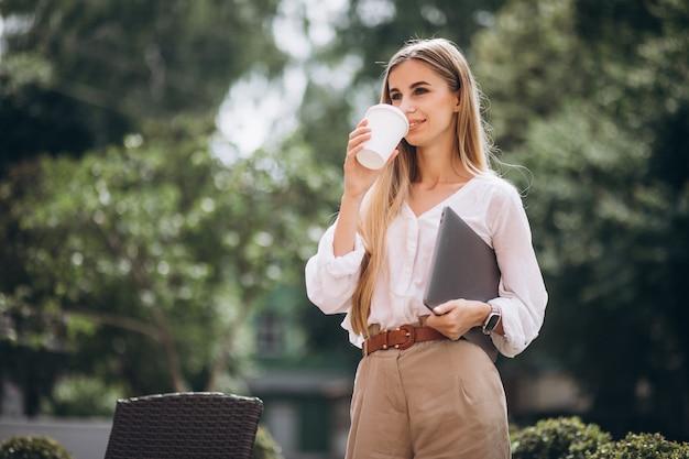 Młoda biznesowa kobieta pije kawę na zewnątrz kawiarni z laptopem