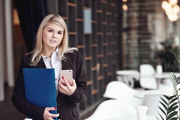 Młoda biznesowa kobieta pisze wiadomości na mądrze telefonie i ono uśmiecha się w biurze