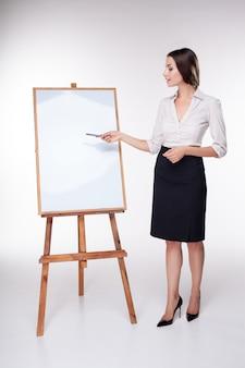 Młoda biznesowa kobieta pokazuje coś na białej ścianie