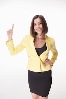 Młoda biznesowa kobieta pokazuje coś na białym tle