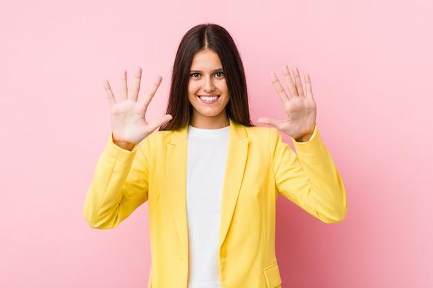 Młoda biznesowa kobieta pokazuje liczbę dziesięć z rękami.