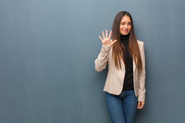 Młoda biznesowa kobieta pokazuje numer pięć